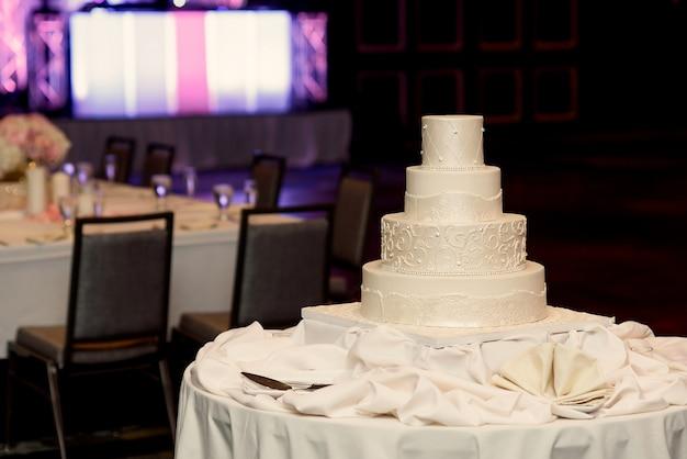 La torta nuziale bianca stanca si leva in piedi sul panno di seta in un pranzo