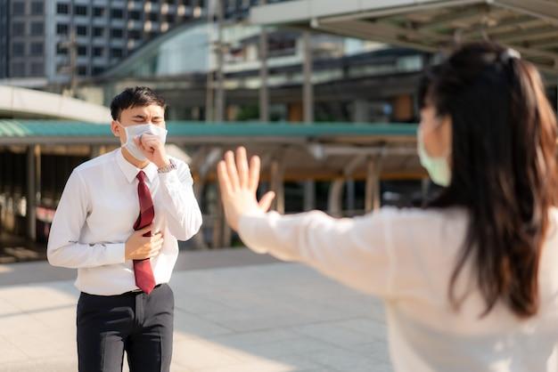 La tosse asiatica dell'uomo d'affari malato con maschera e segnale di stop della donna di affari lo passa per proteggere la distanza dai virus covid-19 e dalle persone che prendono le distanze sociali per il rischio di infezione