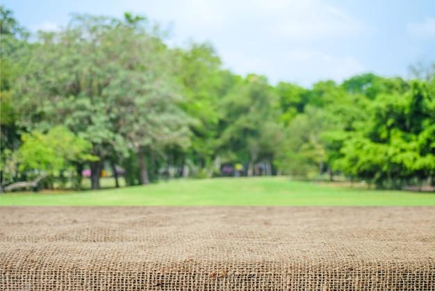 La tovaglia vuota del sacco e della tavola sopra sfuocatura parcheggia con il fondo del bokeh