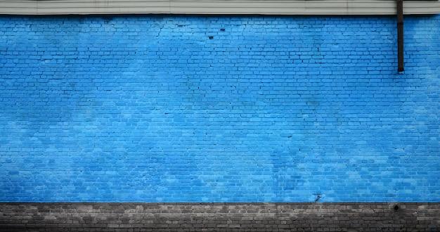 La trama del muro di mattoni di molte file di mattoni dipinti in colore blu