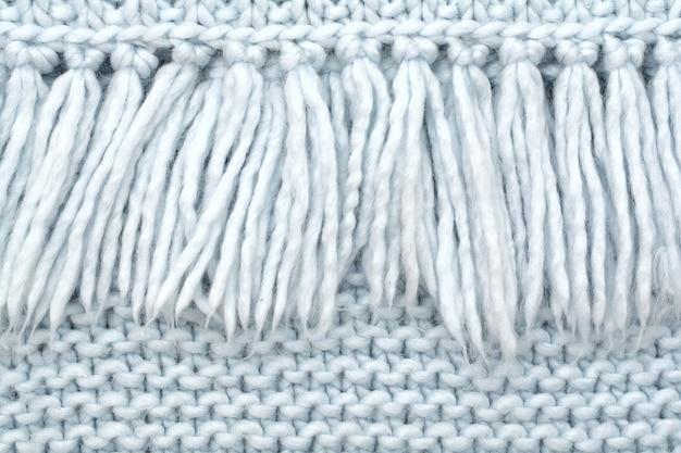 La trama del tessuto a maglia di lana con passanti ad anello con frangia.