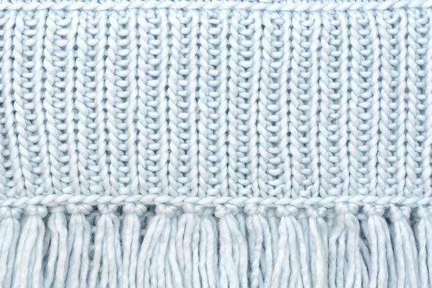 La trama del tessuto di lana a maglia dagli anelli anteriori con frangia.