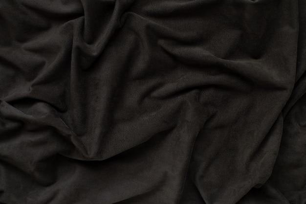 La trama del tessuto in pelle scamosciata marrone scuro, verde oliva ondeggia sulla superficie del tessuto sfondo, carta da parati