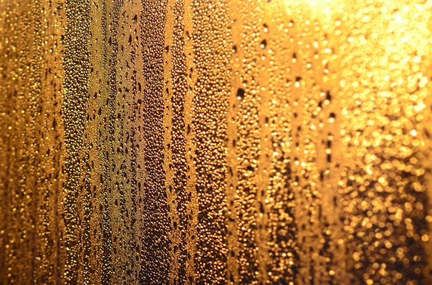 La trama del vetro appannato con un sacco di gocce e gocce di condensa contro la luce del sole all'alba