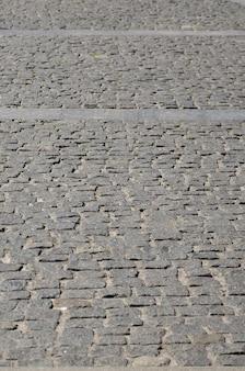 La trama della lastra di pavimentazione (pietre per lastricati) di molte piccole pietre di forma quadrata sotto la luce del sole