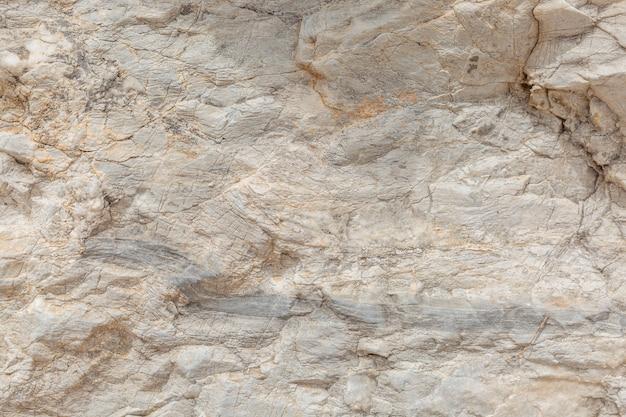 La trama della superficie della pietra naturale, primo piano. materiale da costruzione di antiche civiltà. sfondo. spazi per il testo.
