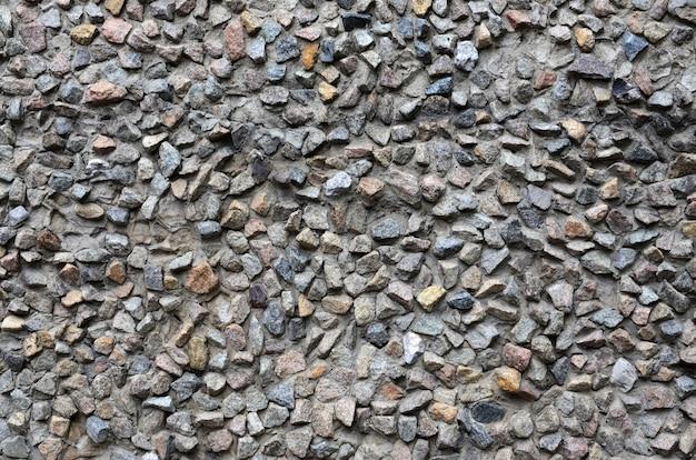 La trama di un forte muro di pietra di molte pietre cementate