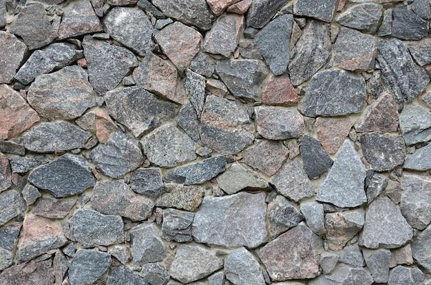 La trama di un forte muro di pietra di molte pietre concrezionate di varie forme