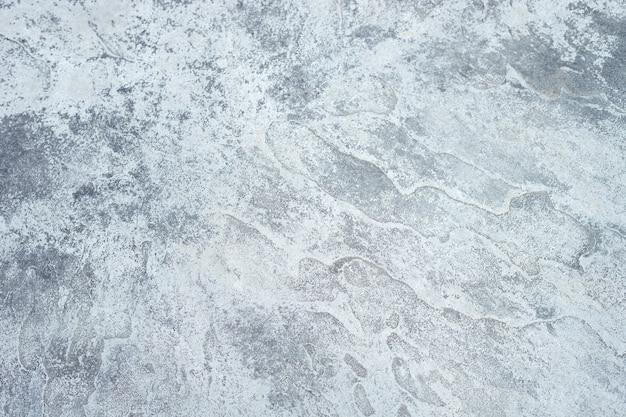 La trama ruvida del muro di cemento grigio.