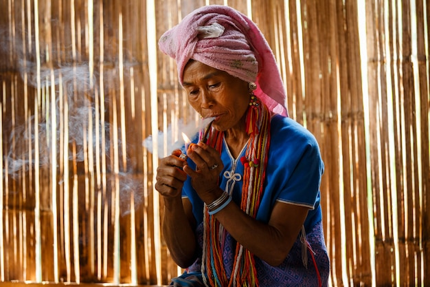 La tribù femminile della collina di karen sta fumando la pipa di tabacco tradizionale nel cottage della tailandia del nord