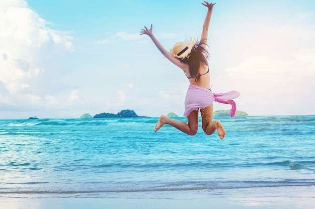 La vacanza sexy in libertà della donna si distende sulla spiaggia e si gode di corsa e salto in mare