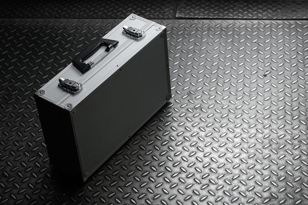 La valigia di ferro in alluminio con serrature su uno sfondo di metallo