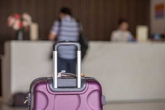 La valigia su hotel controlla in contro fondo, prenotazione e concetto di viaggio.
