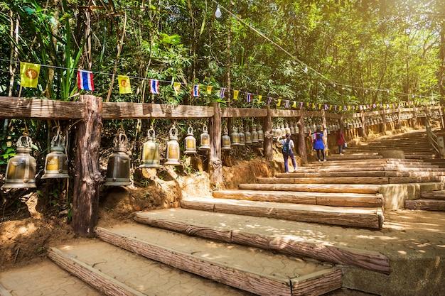 La vecchia campana è appesa alla ringhiera di acciaio nella pietra con l'impronta del signore buddha