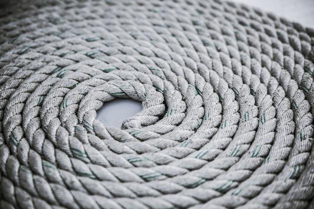 La vecchia corda di ormeggio logora ha rotolato in un cerchio