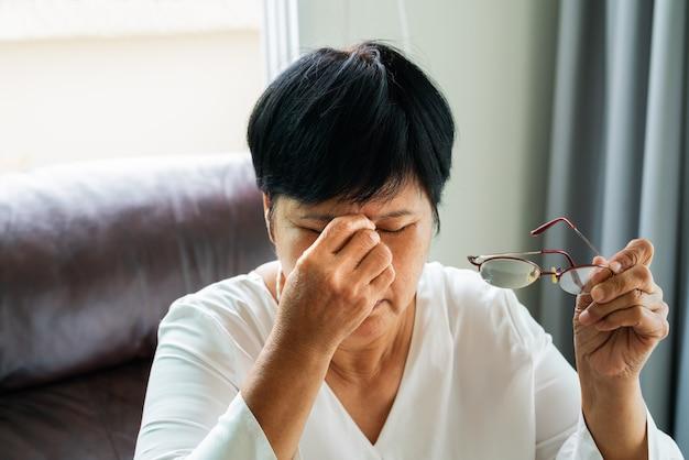 La vecchia donna stanca rimuove gli occhiali, massaggia gli occhi dopo il libro letto.