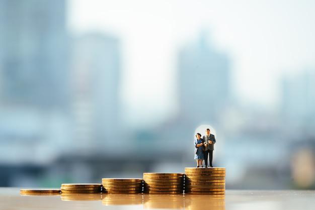 La vecchia figura delle coppie che si leva in piedi in cima alla pila di moneta con gli ambiti di provenienza della città.