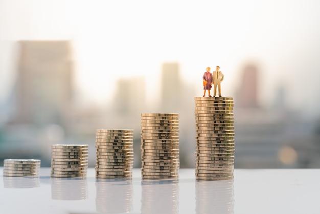 La vecchia figura delle coppie che si leva in piedi in cima alla pila di moneta.