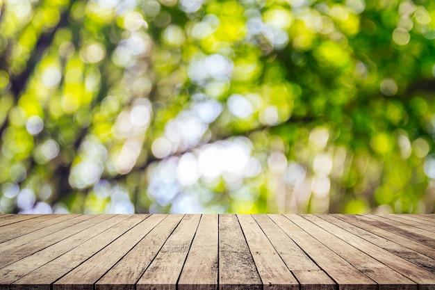 La vecchia plancia di legno con verde naturale astratto ha offuscato il fondo del bokeh per l'esposizione del prodotto