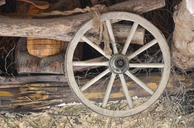 La vecchia ruota di legno della carrozza è appesa al muro del fienile ucraino