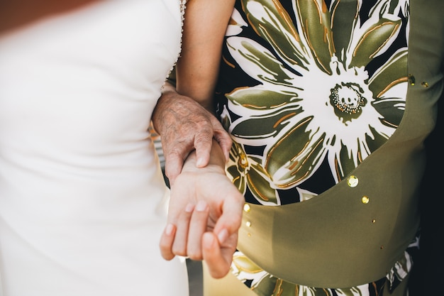 La vecchia signora in vestito verde tiene la mano della sposa tenera