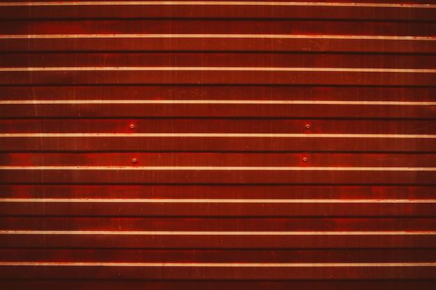 La vecchia superficie di metallo macchiata e trasandata rossa con i bulloni si chiude su.