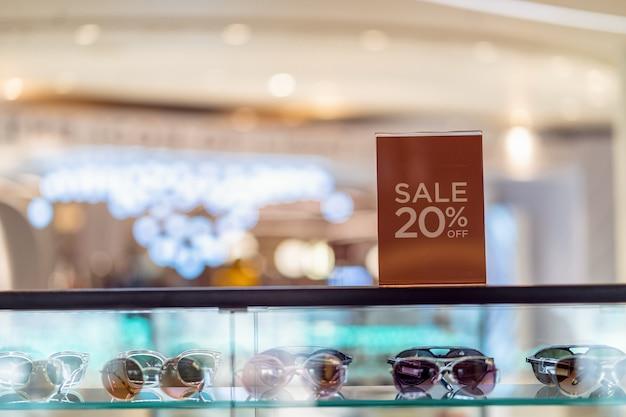 La vendita 20 fuori mock up annuncia l'impostazione della cornice dello schermo sopra l'armadietto di vetro nello shopping