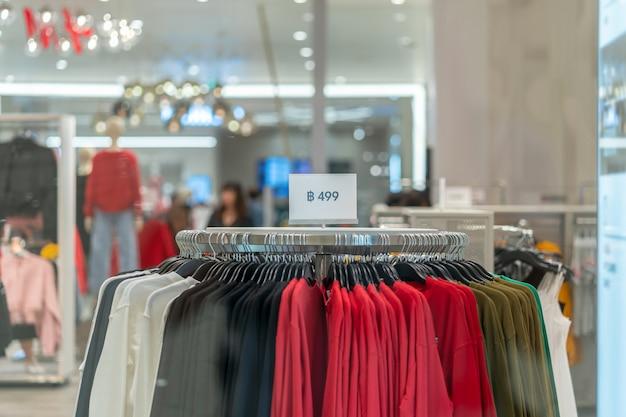 La vendita fuori mock up pubblicizza la cornice del display sopra la linea di vestiti nel reparto commerciale