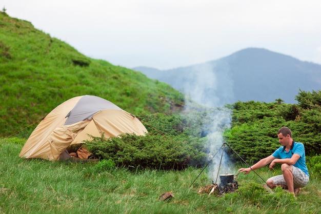 La viandante che prepara l'alimento in una bombetta sul fuoco di campeggio in montagne si avvicina alla tenda