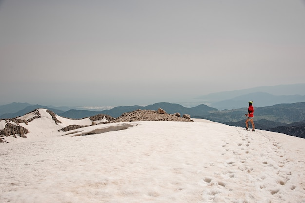 La viandante femminile viaggia con i bastoni da passeggio in montagne