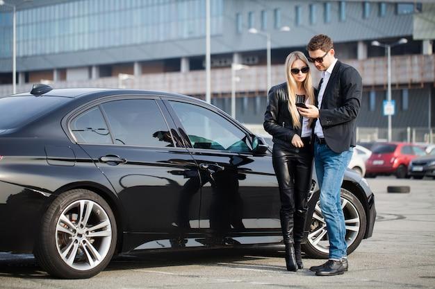 La visita di successo alla concessionaria. la giovane coppia felice sceglie e acquista una nuova auto per la famiglia