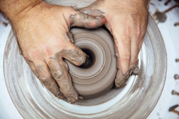 La vista ad un artista crea ceramiche su una ruota girevole