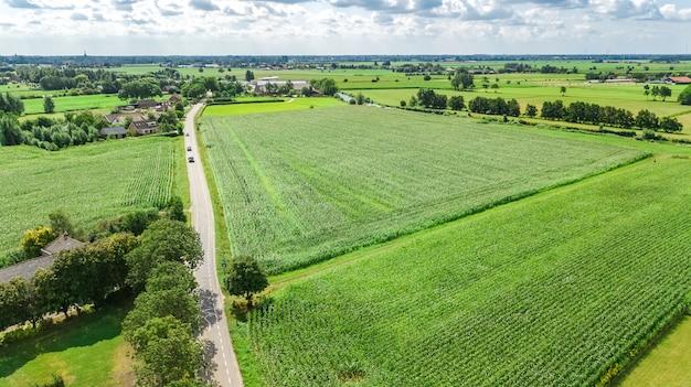 La vista aerea del fuco dei campi verdi e le case dell'azienda agricola si avvicinano al canale da sopra, paesaggio olandese tipico, olanda, paesi bassi
