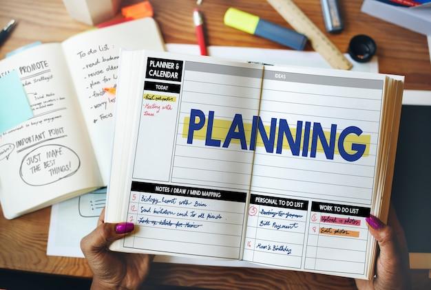 La vista aerea del primo piano delle mani aperte organizza il libro con la parola di pianificazione