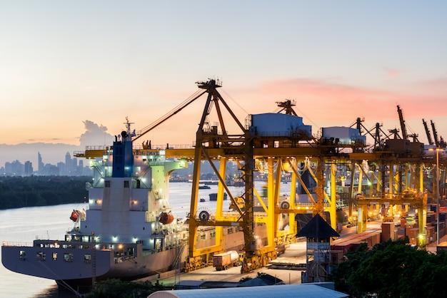La vista aerea della porta del contenitore di carico di bangkok nell'uso di sera per la logistica, importa, esporta il fondo
