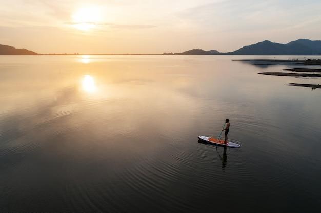 La vista aerea della siluetta di sta sul pensionante della pagaia che rema al tramonto su un fiume calmo caldo piano.