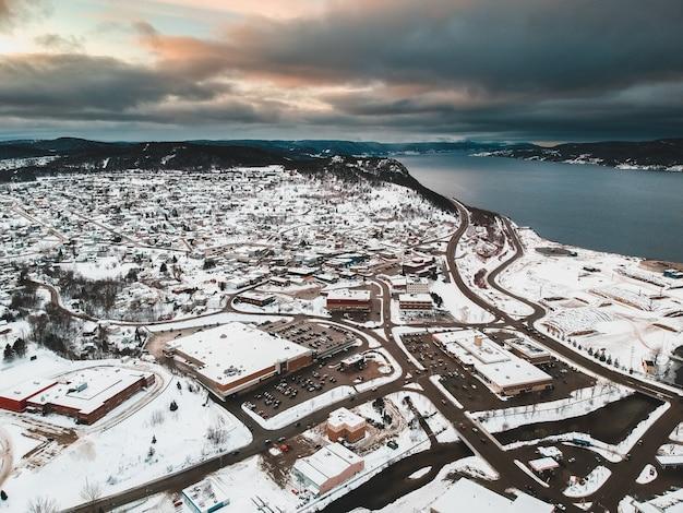 La vista aerea delle case innevate si avvicina al corpo idrico sotto il cielo nuvoloso durante l'ora dorata
