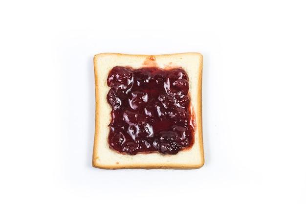 La vista aerea delle fragole rosse luminose conserva, si sviluppa su una fetta di pane bianco