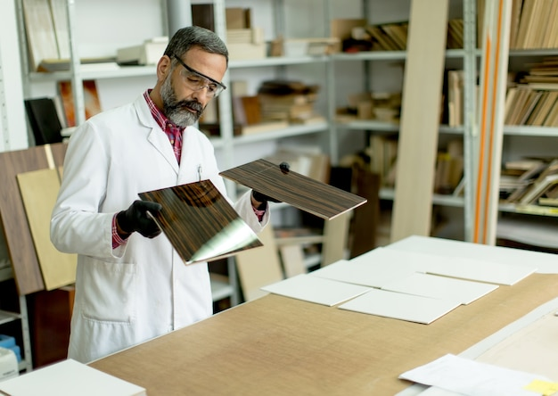 La vista all'ingegnere in laboratorio esamina le piastrelle di ceramica