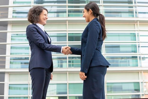 La vista dal basso dei colleghi allegri che stringono le mani si avvicina alla costruzione. giovani donne che indossano abiti formali incontro all'aperto. concetto di stretta di mano di affari