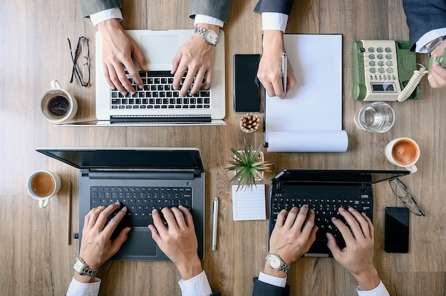 La vista dall'alto dei coworking sta lavorando su laptop e documenti cartacei.