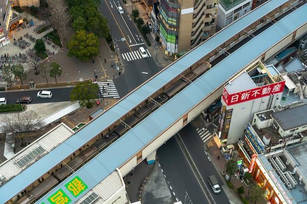 La vista dall'alto dei pedoni affolla la gente irriconoscibile che aspetta e cammina nel treno alla stazione ferroviaria