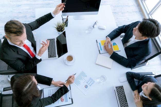 La vista dall'alto del team aziendale durante la conferenza di incontro sono documenti di lavoro sul piano di marketing.