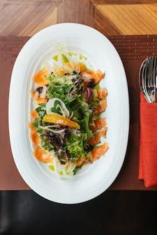 La vista dall'alto dell'insalata di pomelo di salmone affumicato include quercia verde, lattuga a foglia rossa e cipolla.