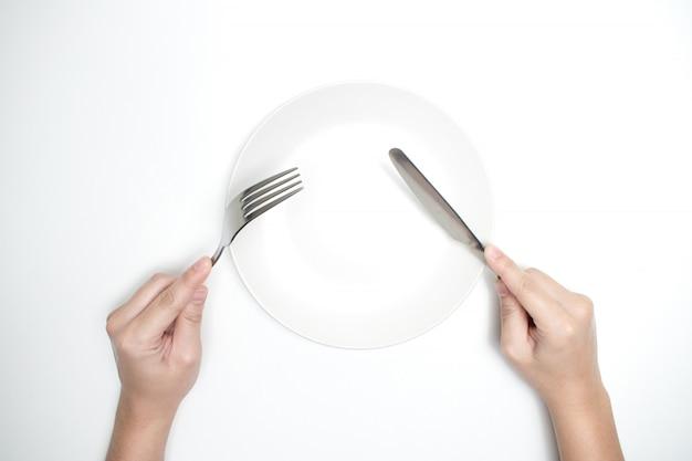 La vista dall'alto della mano che tiene un cucchiaio e un coltello