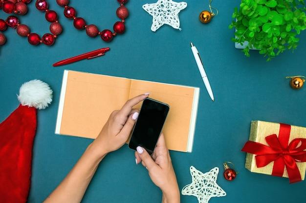 La vista dall'alto delle mani femminili con telefono e decorazioni natalizie