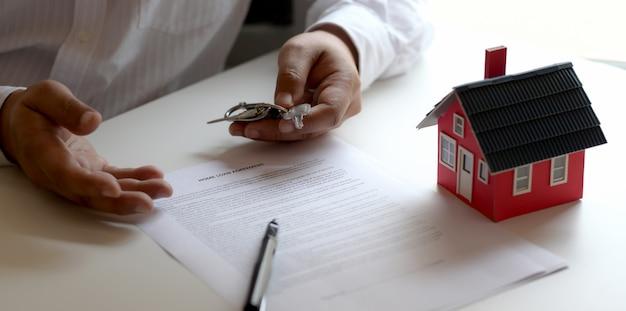 La vista del primo piano dell'agente immobiliare maschio offre la chiave per il suo cliente dopo la firma del contratto di locazione locativo