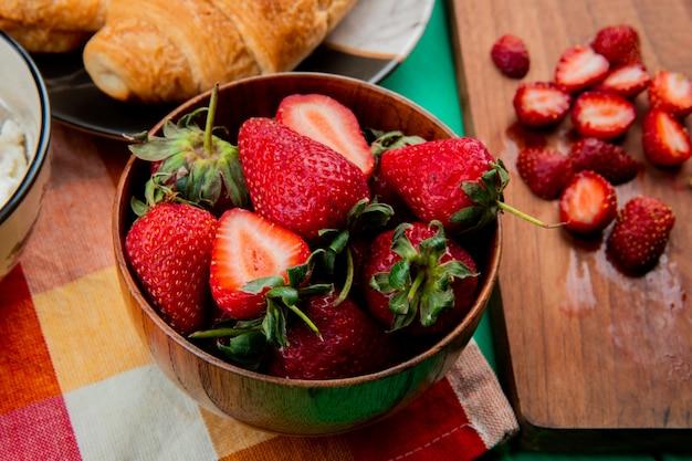 La vista del primo piano della ciotola di fragole con mezzaluna arriva a fiumi il piatto sul panno e le fragole tagliate sul tagliere