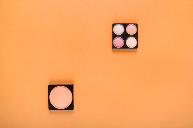 La vista dell'angolo alto del fard e dell'ombretto spolverizza su fondo arancio