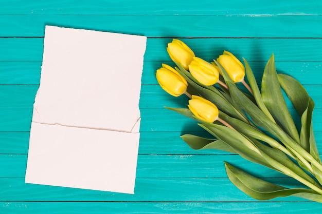 La vista dell'angolo alto del tulipano giallo fiorisce con carta in bianco bianca sullo scrittorio verde